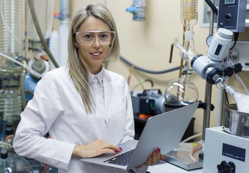 Mulher com o laptop que trabalha no laboratório químico fotos de stock
