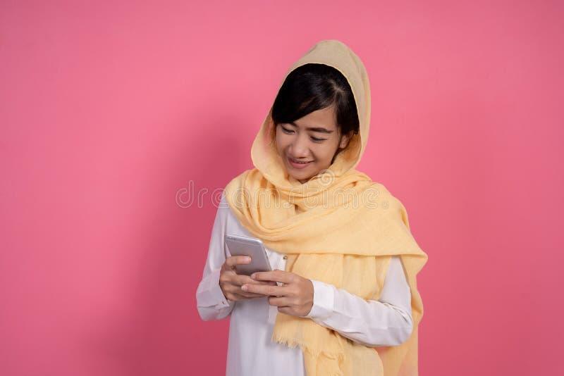 Mulher com o lenço que texting usando seu telefone esperto fotografia de stock