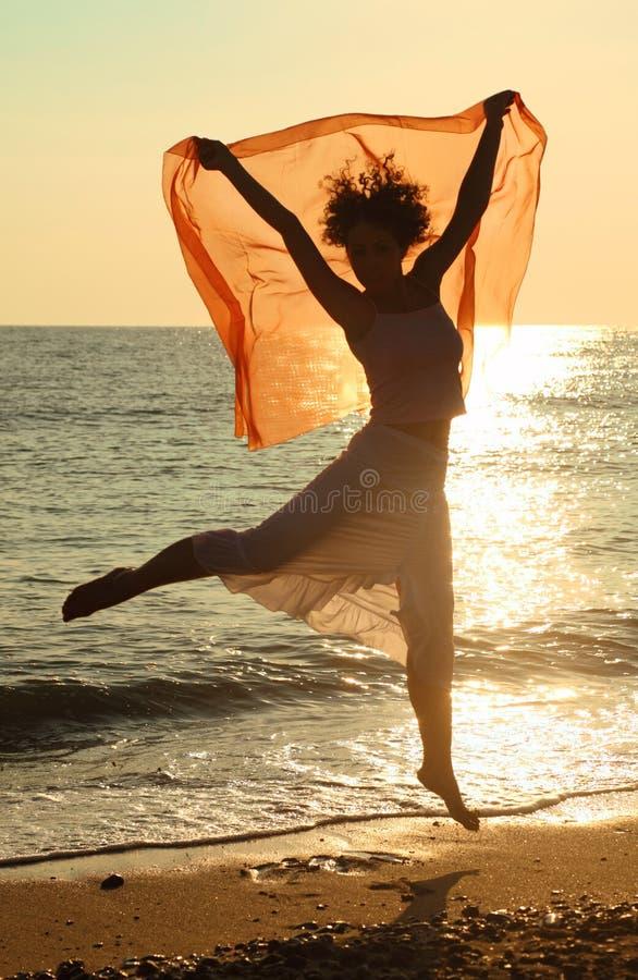Mulher com o lenço vermelho que salta na praia foto de stock