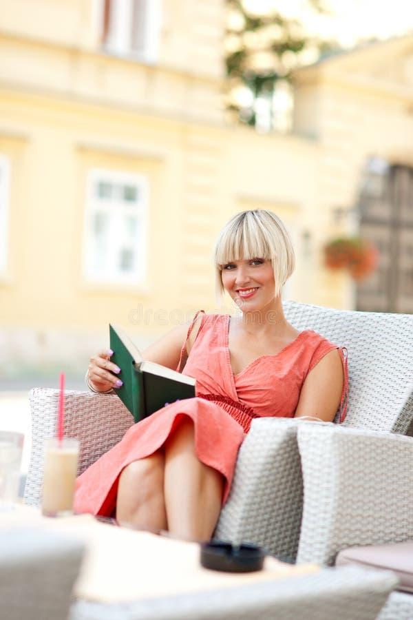 Mulher com o livro no café fotos de stock royalty free