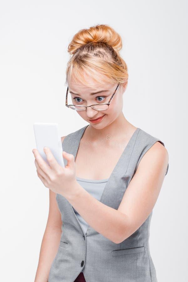 Mulher com o móbil chocado, confundido e deixado perplexo fotos de stock