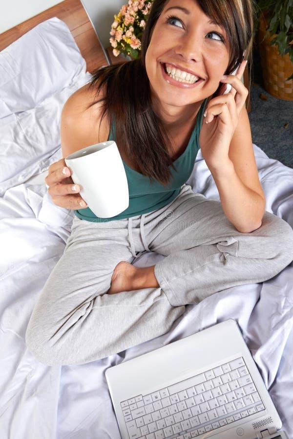 Mulher com o móbil na cama foto de stock