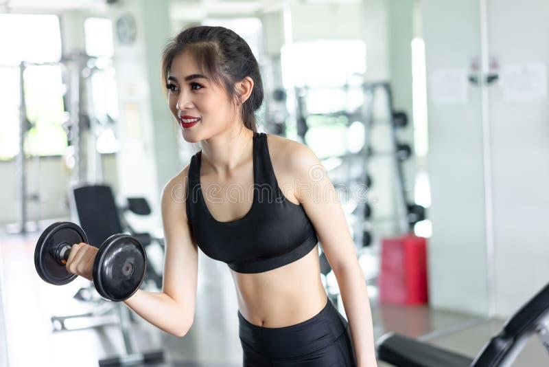 Mulher com o músculo do exercício do exercício do peso imagens de stock royalty free