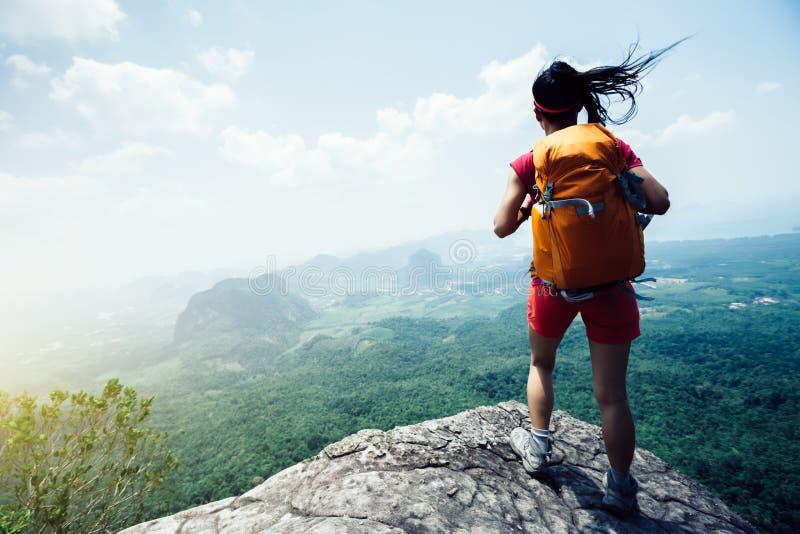 Mulher com o mochileiro que caminha na borda do penhasco da montanha do beira-mar fotos de stock