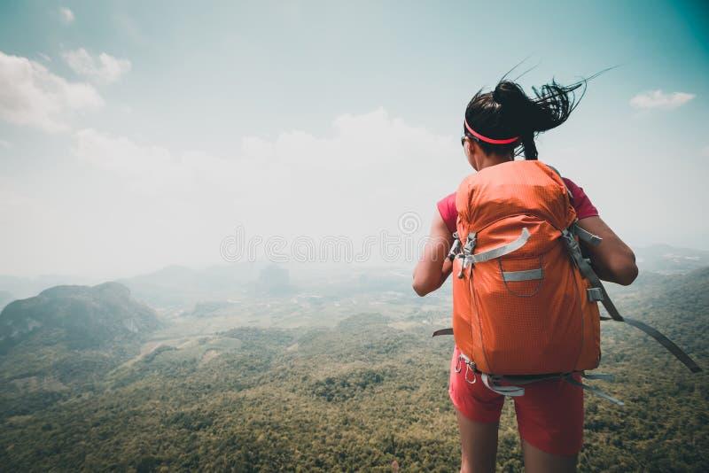 Mulher com o mochileiro que caminha na parte superior da montanha imagens de stock