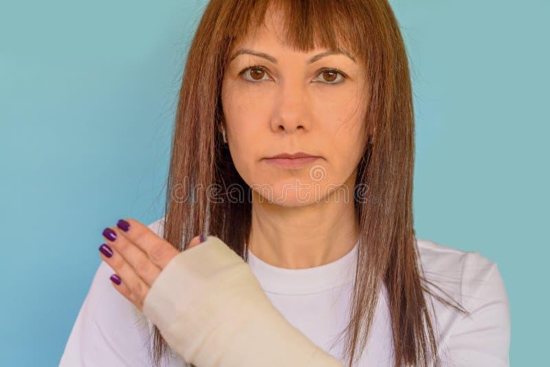 Mulher com o osso de braço quebrado no molde, mão emplastrada no fundo azul fotografia de stock royalty free