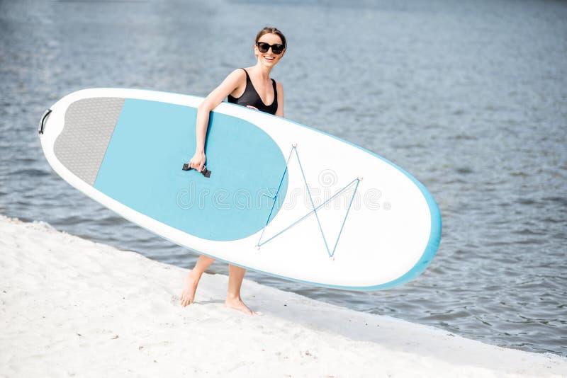 Mulher com o paddleboard standup na praia fotos de stock royalty free