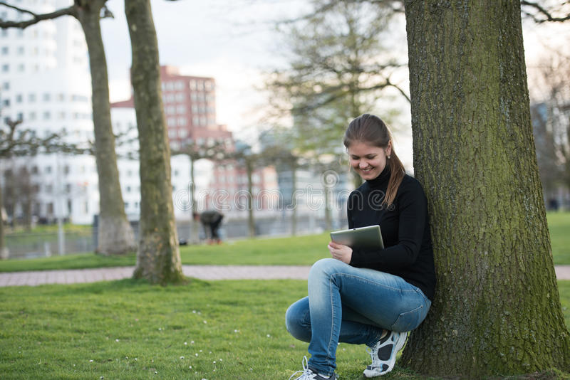 Mulher com o PC da tabuleta no parque foto de stock royalty free
