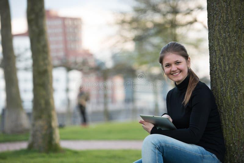 Mulher com o PC da tabuleta no parque imagens de stock royalty free