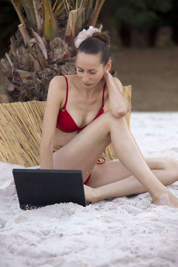 Mulher com o portátil na praia imagens de stock royalty free