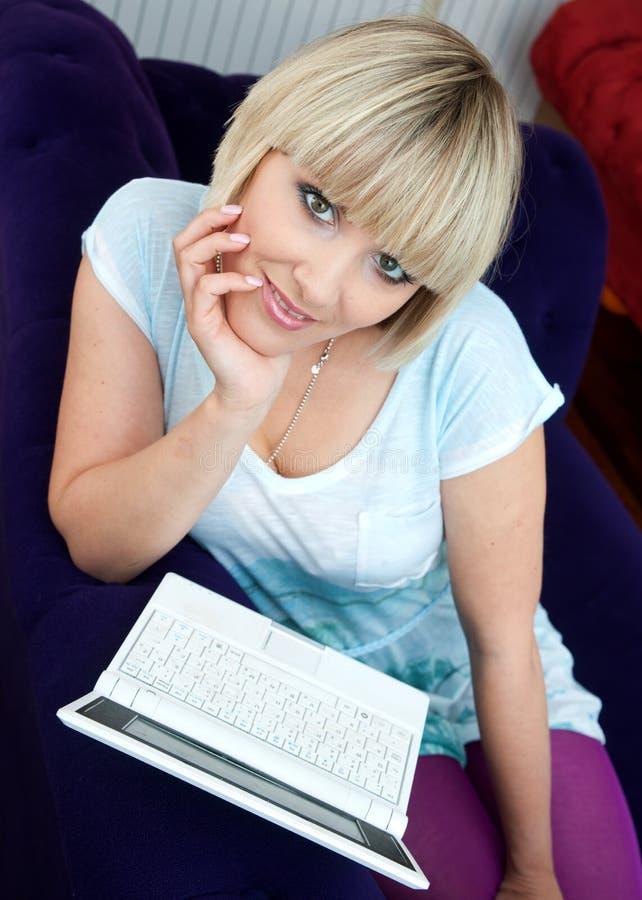 Mulher com o portátil no sofá fotos de stock royalty free