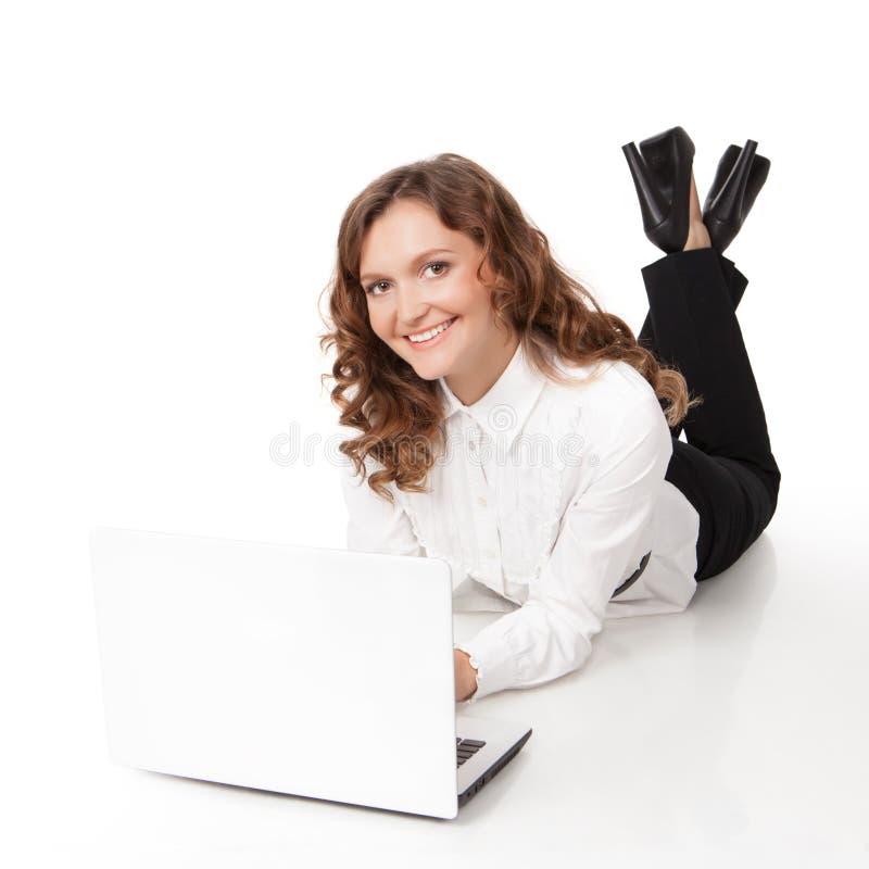 Mulher com o portátil que encontra-se para baixo no assoalho fotos de stock