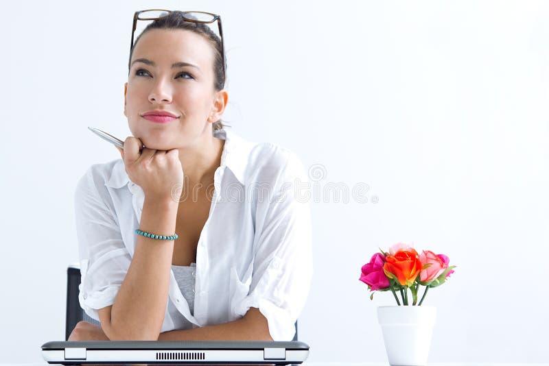 Mulher com o portátil que trabalha em casa