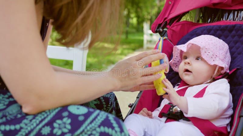 Mulher com o Pram que senta-se no banco no parque imagem de stock