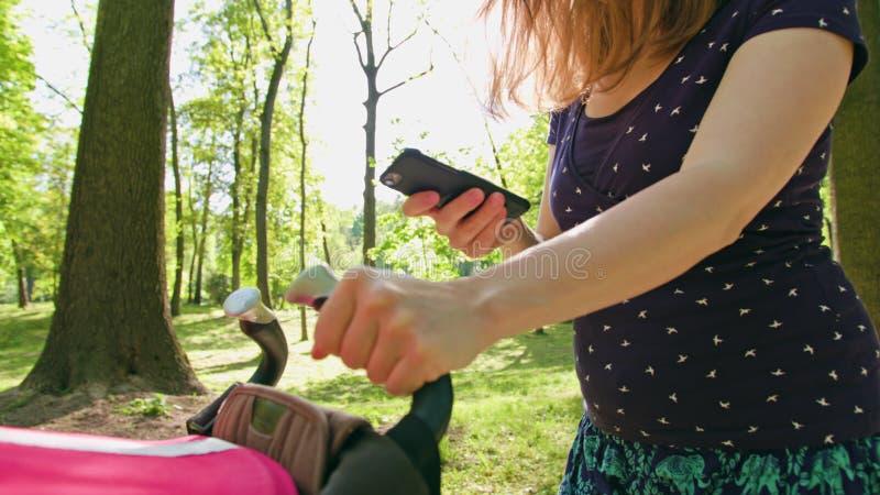 Mulher com o Pram que toma uma caminhada e que usa um telefone imagem de stock