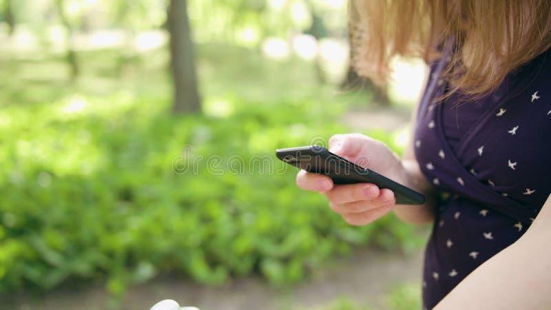 Mulher com o Pram que toma uma caminhada e que usa um telefone imagens de stock
