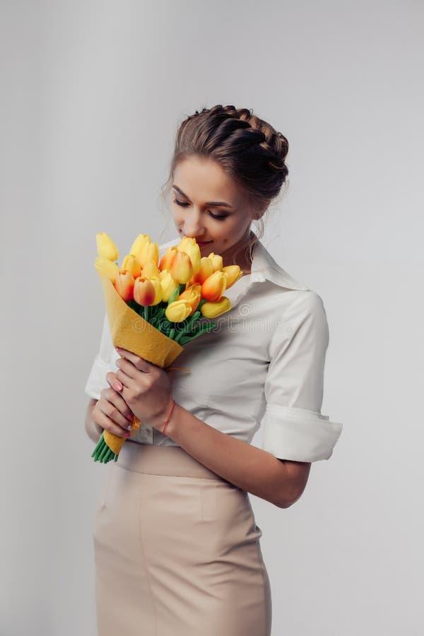 Mulher com o ramalhete da flor da mola Flores de cheiro surpreendidas felizes da mulher modelo imagem de stock