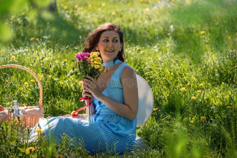 Mulher com o ramalhete das flores no piquenique imagem de stock