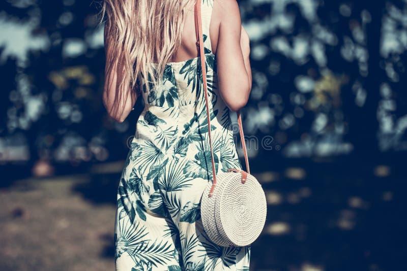 Mulher com o saco à moda elegante do rattan e o lenço da seda fora Ilha tropical de Bali, Indonésia Bolsa do Rattan e fotografia de stock royalty free