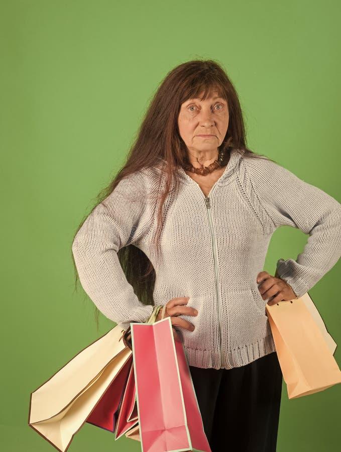 Mulher com o saco de compras colorido da posse vermelha longa do cabelo imagem de stock royalty free