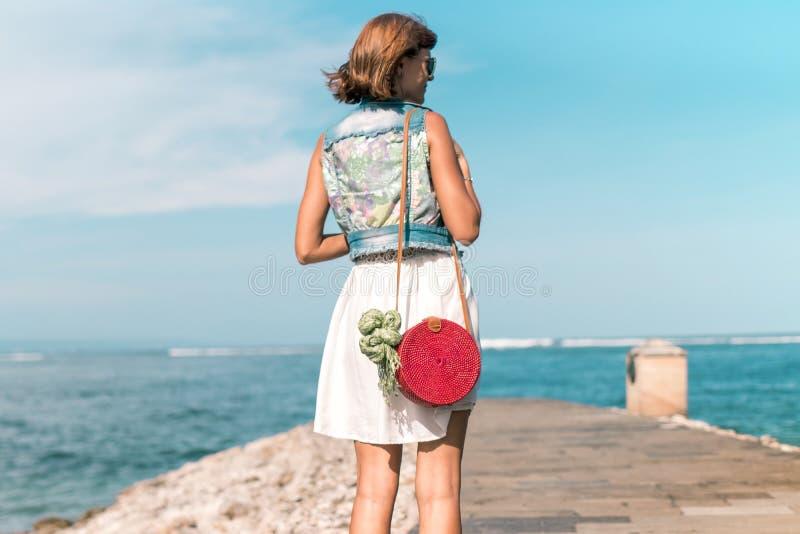 Mulher com o saco vermelho à moda elegante do rattan e o lenço da seda fora Ilha tropical de Bali, Indonésia Bolsa do Rattan fotografia de stock