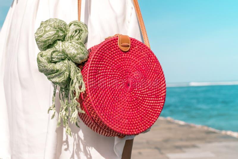 Mulher com o saco vermelho à moda elegante do rattan e o lenço da seda fora Ilha tropical de Bali, Indonésia Bolsa do Rattan imagens de stock royalty free