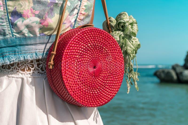 Mulher com o saco vermelho à moda elegante do rattan e o lenço da seda fora Ilha tropical de Bali, Indonésia Bolsa do Rattan fotografia de stock royalty free