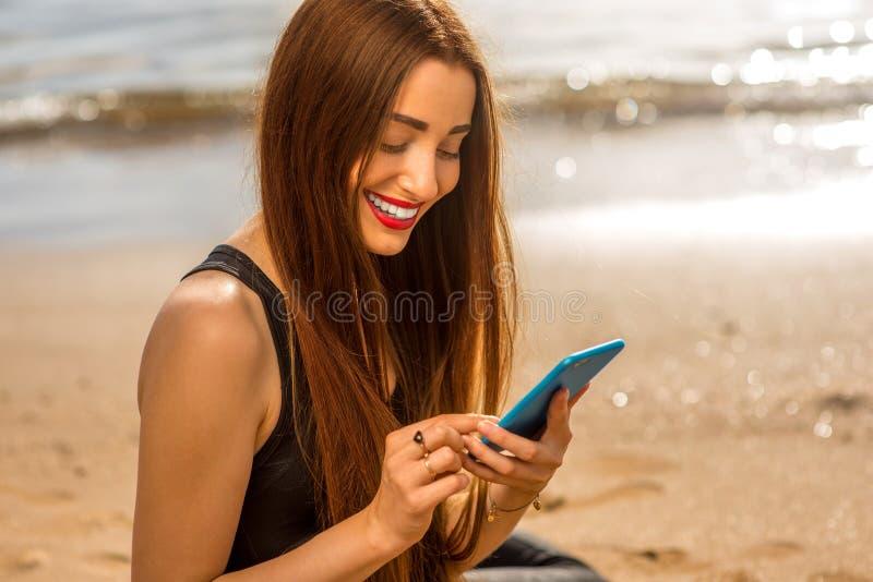 Mulher com o smartphone na praia imagem de stock royalty free