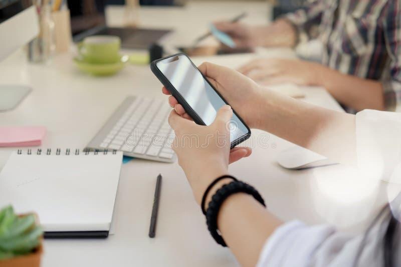 mulher com o smartphone no escritório fotos de stock royalty free