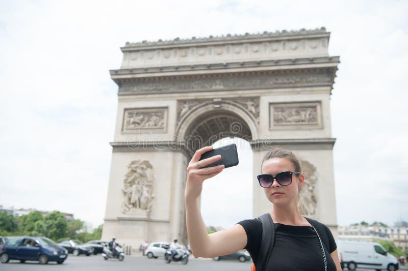Mulher com o smartphone no monumento do arco em Paris, france A mulher faz o selfie com o telefone em Arco do Triunfo Férias e si fotos de stock