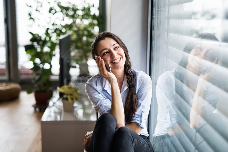 Mulher com o smartphone pela janela em casa, fazendo um telefonema imagens de stock royalty free