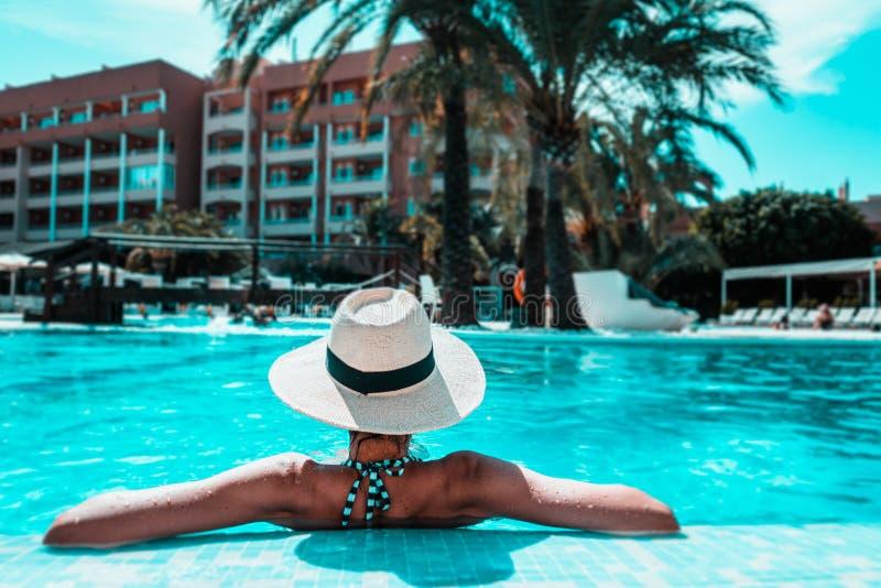 Mulher com o sunhat que relaxa na piscina no spa resort fotografia de stock
