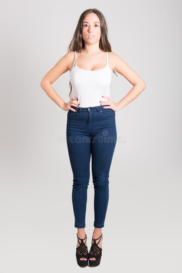 Mulher com o t-shirt branco vestindo e a calças de ganga do cabelo longo foto de stock