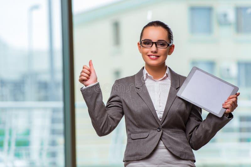 A mulher com o tablet pc no conceito do negócio fotografia de stock