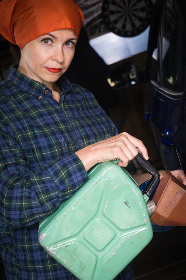Mulher com o tanque metálico do carro do enchimento do cartucho imagens de stock royalty free