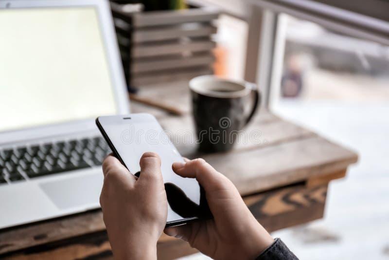 Mulher com o telefone celular e o portátil que sentam-se na tabela, close up fotos de stock