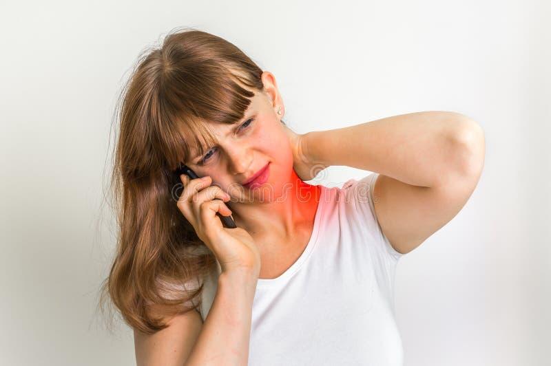 Mulher com o telefone celular que tem a dor em seu pescoço imagens de stock