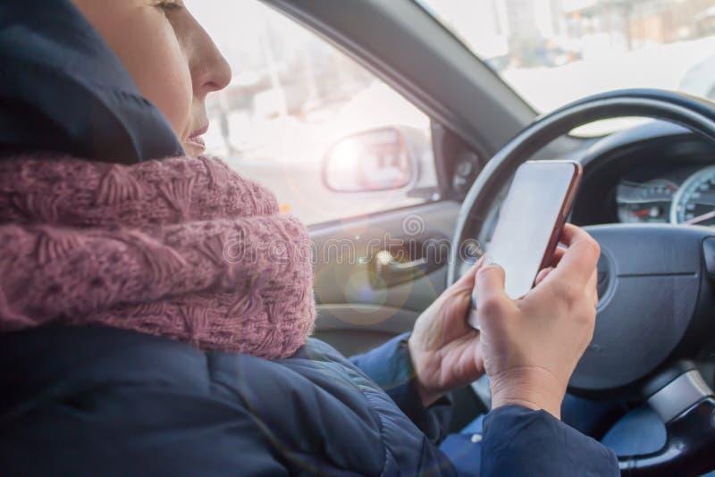 Mulher com o telefone no assento do ` s do motorista no carro imagens de stock royalty free