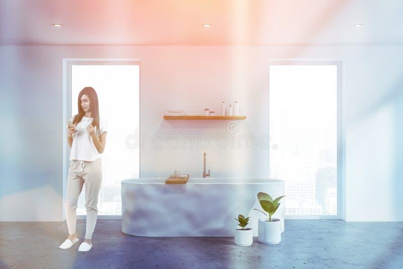 Mulher com o telefone no banheiro branco foto de stock royalty free