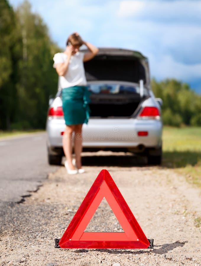 Mulher com o telefone perto do carro quebrado foto de stock
