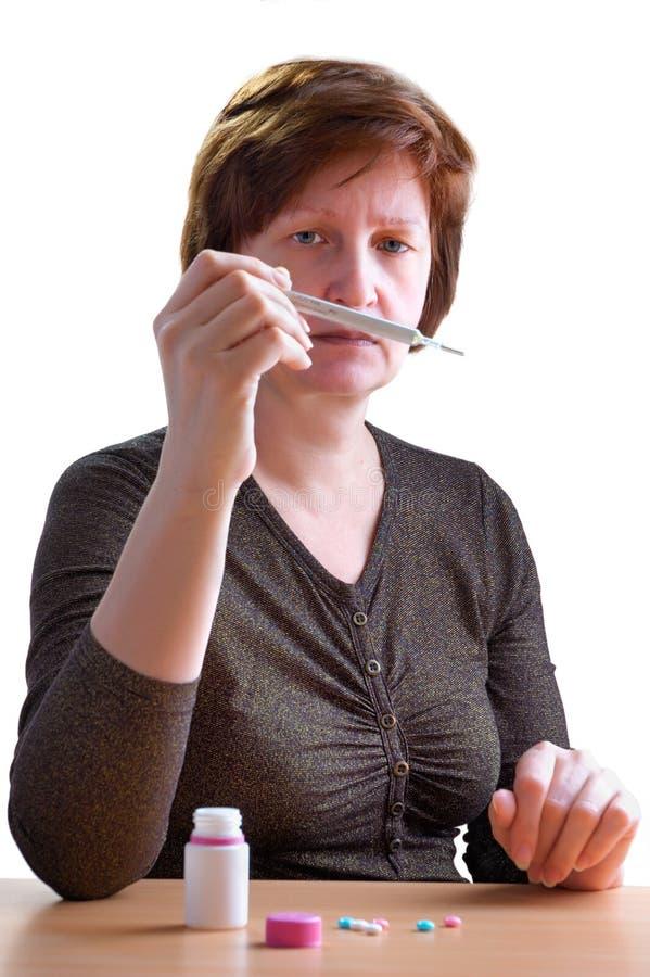 Mulher com o termômetro em uma mão fotos de stock royalty free