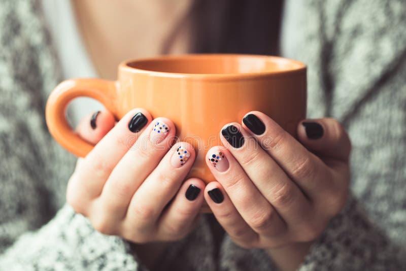 Mulher com o tratamento de mãos bonito que guarda um copo alaranjado do cacau fotografia de stock royalty free