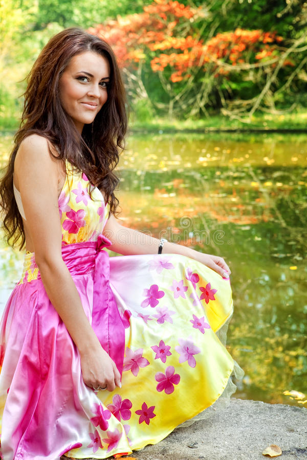 Mulher com o vestido colorido bonito perto do lago imagem de stock royalty free