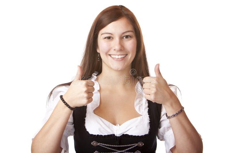 A mulher com o vestido do Dirndl de Oktoberfest mostra os polegares imagens de stock royalty free
