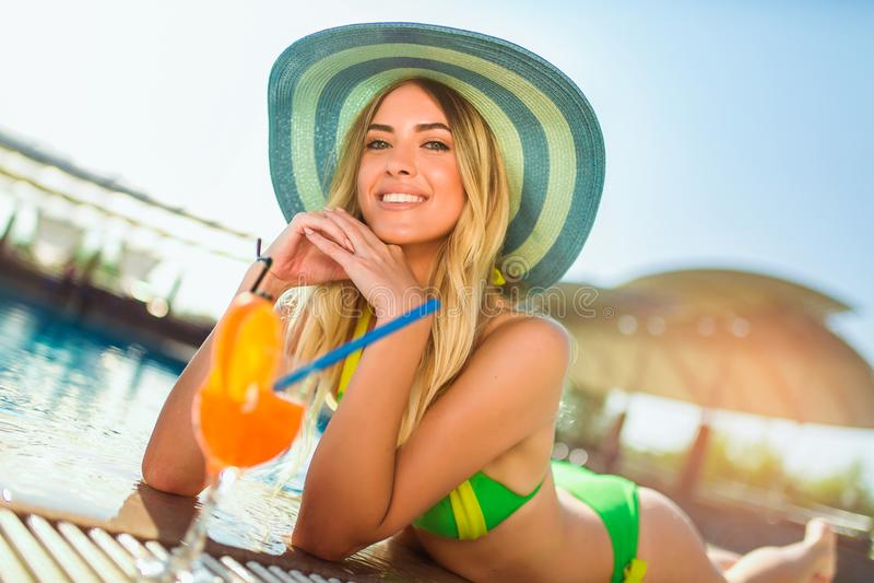 mulher com o vidro de cocktail que refrigera no sol tropical perto da piscina em uma cadeira de plataforma foto de stock royalty free