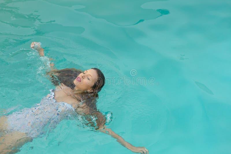 A mulher com olhos fechou a flutuação na piscina no quintal da casa fotos de stock royalty free