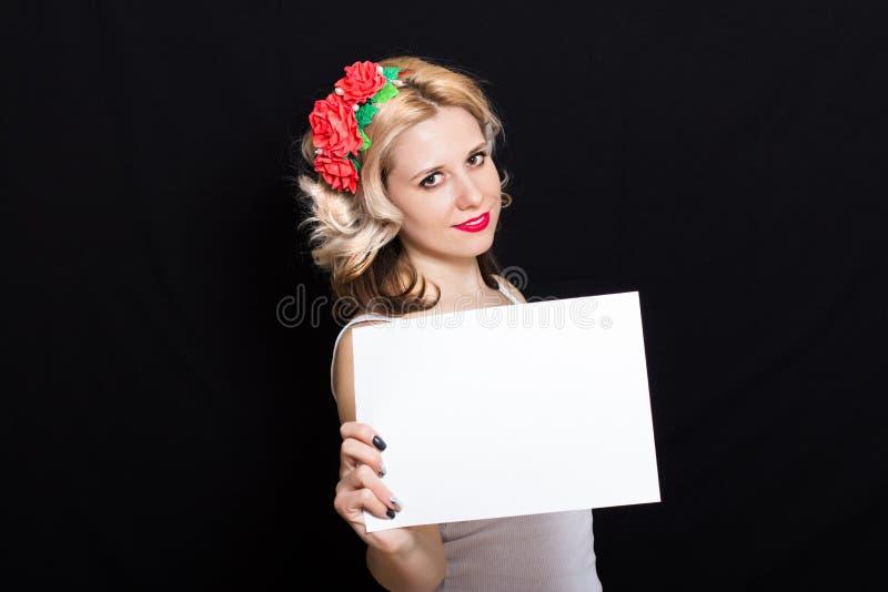 Mulher com ondas do louro e batom vermelho na borda com guardar vermelho das flores fotografia de stock