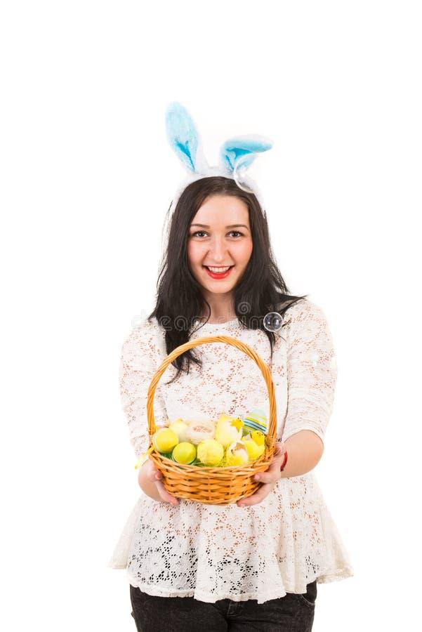 A mulher com orelhas do coelho dá a cesta da Páscoa imagem de stock