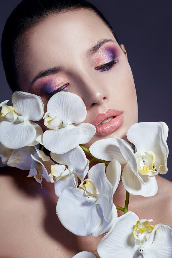 Mulher com a orquídea branca perto da menina da cara com batom brilhante bonito do rosa da composição Cosméticos delicados da pro imagem de stock