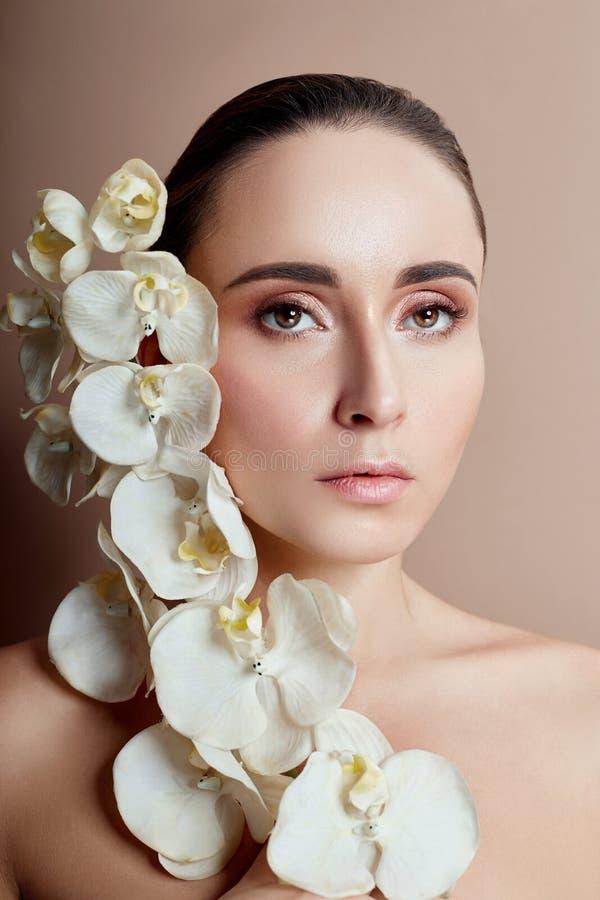 Mulher com a orquídea branca perto da menina da cara com batom brilhante bonito do rosa da composição Cosméticos delicados da pro imagens de stock royalty free